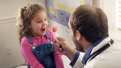 A doctor gives a girl a lollipop after teaching her about executive function.