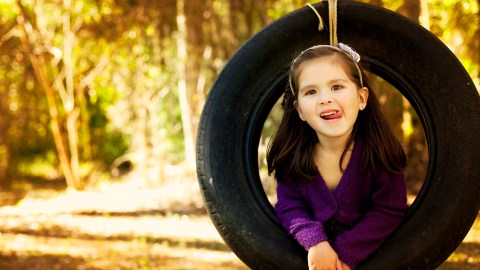 A girl with SPD sits in a tire swing.