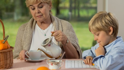 Grandma pouring tea while her grandson works on homework without frustration