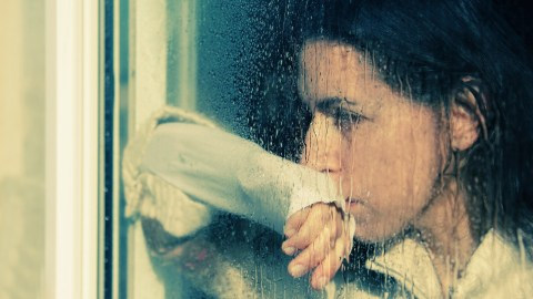 A woman looking through a rainy window and doing negative self talk
