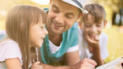 A father reads with his two kids in the park. Spending quality time together is one strategy for how to be a better dad.