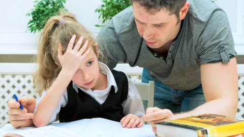 A father helping his daughter improve her education by completing her homework
