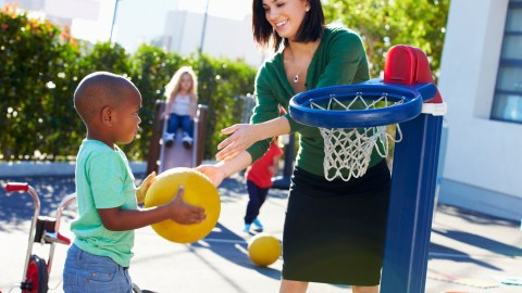 A teacher playing with a child as recess to help improve his education
