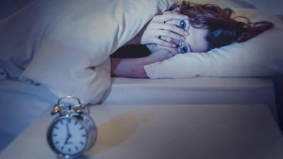 Woman in bed with ADHD and sleeplessness covering face while looking at alarm clock on bedside table