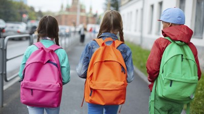 Three students with ADHD and colorful backpacks walk to school on city street