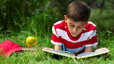 Teen boy with ADHD reading a book in the grass