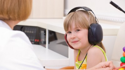 Doctor audiologist testing child's ears on medical equipment for auditory processing disorder