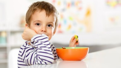 Boy with ADHD eating nutritious breakfast at table with bowl in front of him