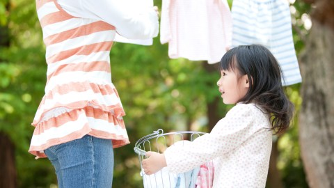 A girl with ADHD helping her mother drying laundry, smiling