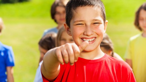 A boy with ADHD gives a thumbs up.