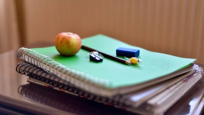 College student's desk with books and an apple