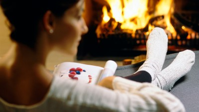 ADHD Woman reading magazine by fireplace
