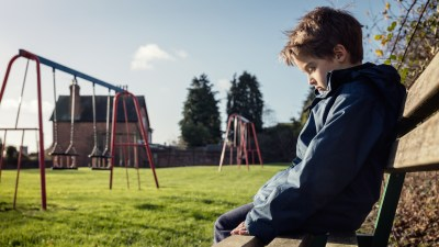 A lonely child sitting alone at recess as a form of school punishment