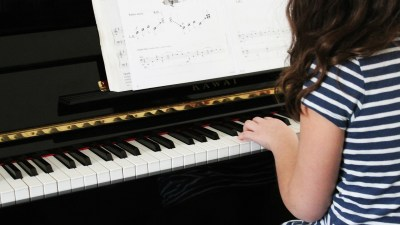 A girl plays the piano, one of many activities to build self esteem besides sports.