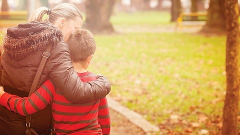 A mother embraces her son in a park and explains the ADHD and behavior connection.