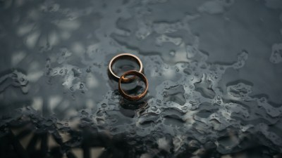 Two wedding rings on a table with raindrops symbolize the marriage advice you need when parenting special needs children