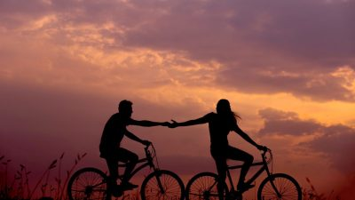 A couple hold hands while bicycling at sunset, represent an adhd couple resolving to work as a team