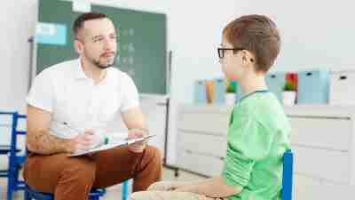 A middle schol-aged child talking with a school professional.