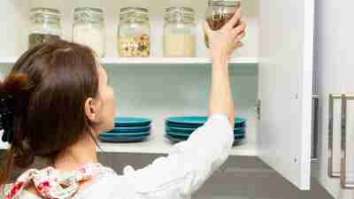 Women picking an item from storage hutch. Smart kitchen organization concept