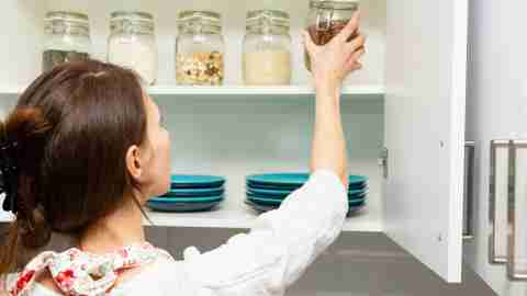 Women picking an item from storage hutch. Smart kitchen organization concept