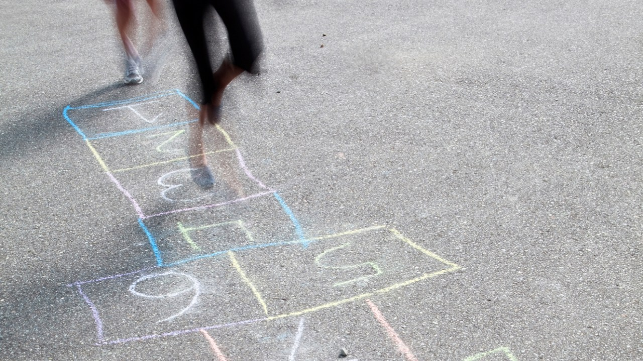 Girls play hopscotch during recess, and recite ADHD statistics