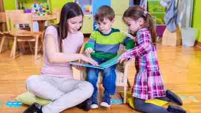 Kindergarten Teacher and Two ADHD Kids Reading a Book