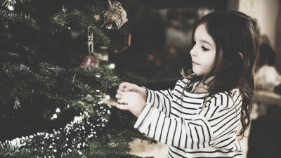 A girl with ADHD decorates a tree, minimizing holiday stress with good behavior
