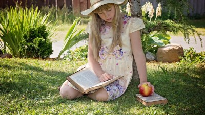 ADHD girl reads a book outside