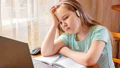 Lethargic girl with concentration deficit disorder (CDD) and ADHD doing remote school
