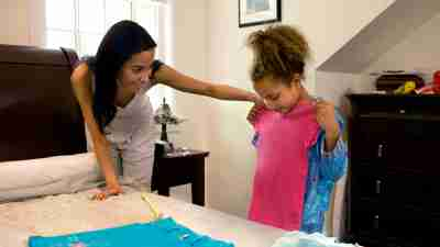 a mother helps her daughter choose her clothes for the next day, a daily habit of the most organized children with ADHD