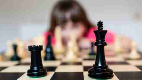 a girl with ADHD keeps her brain sharp during the summer by playing chess