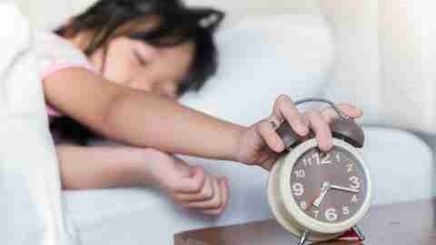 A girl with ADHD turns of her alarm, the first step of her morning routine