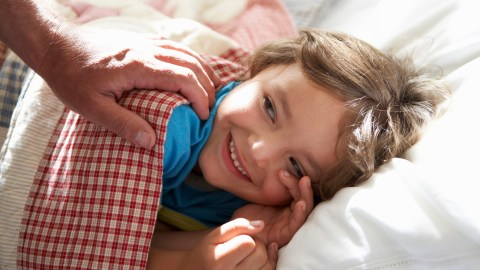 A parent wakes up a child with ADHD to start his morning routine