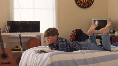 A child relaxs in bed and reads a book for kids with adhd.