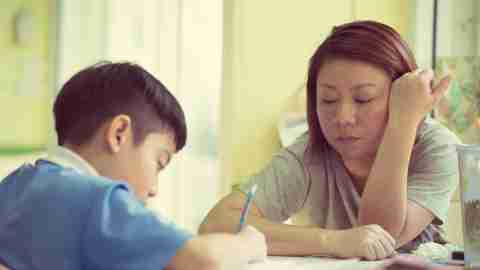 Mom helps boy with homework to help with executive function disorder.