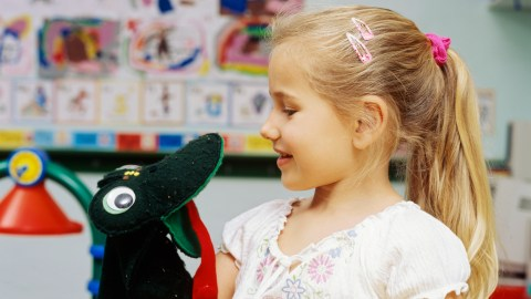 A girl talking to a puppet, a good tool to manage anxiety in young children