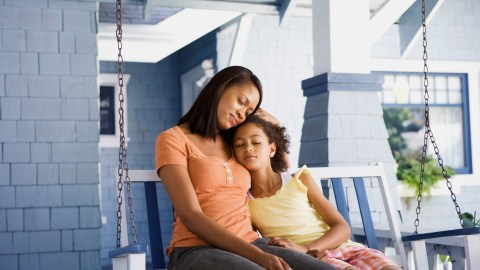 Mother and daughter hugging on porchswing to help the child manage anxiety