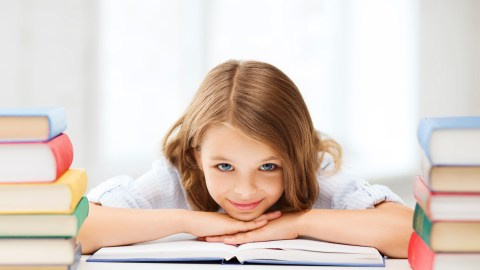 Girl with ADHD focusing with books around her