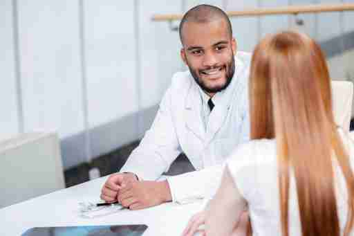 A doctor evaluates his patient for ADHD by talking with her. Diagnosis requires more than just brain imaging.