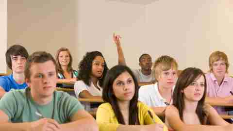 A student raises her hand in class to ask a question about ADHD and college.