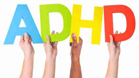 A group of ADHD adults proudly hold up a sign to indicate that ADHD is real.