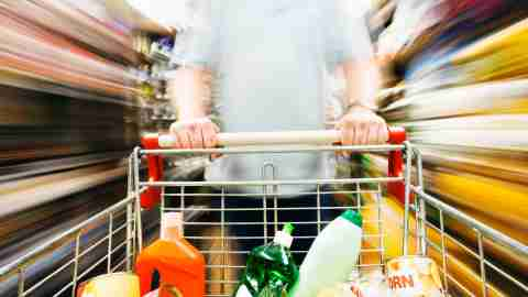 A man who hates grocery shopping is speeding through it to get it over with.