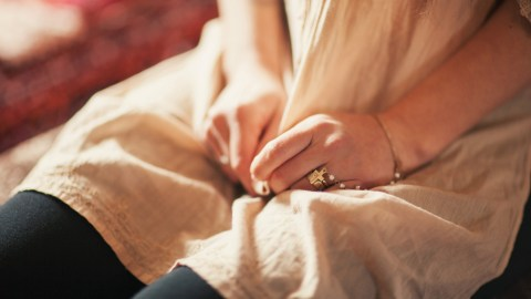 A girl with social anxiety disorder wrings her hands in her lap