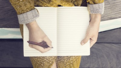 A woman starts to write her expenses in a notebook and realizes she's been spending too much money.