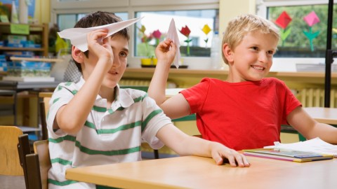 Boys with ADHD throw paper airplanes in class