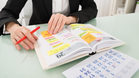 Woman uses her daily planner as she was taught to do in CBT.