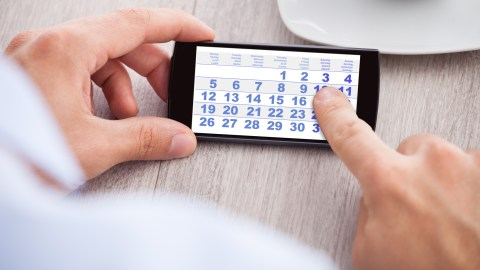 A man uses the digital calendar on his phone.