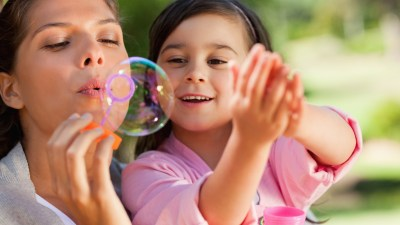 A mom and daughter blow bubbles to practice mindfulness skills.