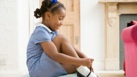 A girl ties her shoes peacefully as she gets ready for school.