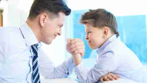 A child with ADHD arm wrestles with his father.